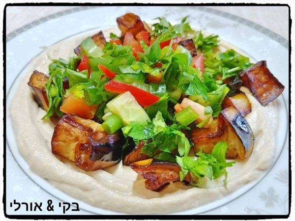 קוביות צ'יפס וקוביות חצילים מטוגנים עם סלט ירקות על מצע של ממרח חומוס ביתי
