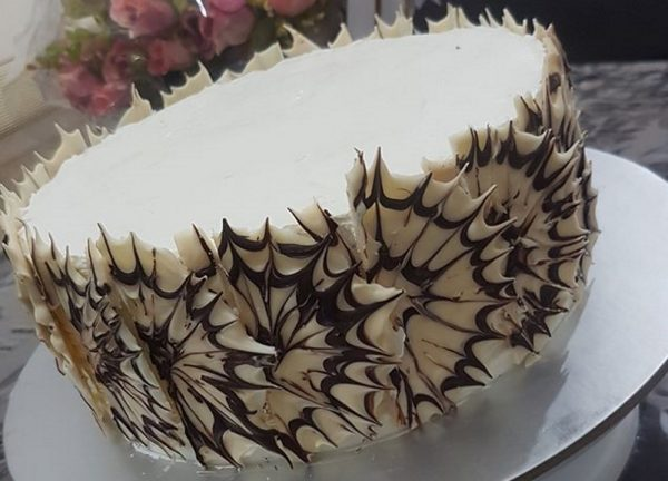 עוגת טורט במילוי ועיטור קצפת ומסביב קישוט קיפוד